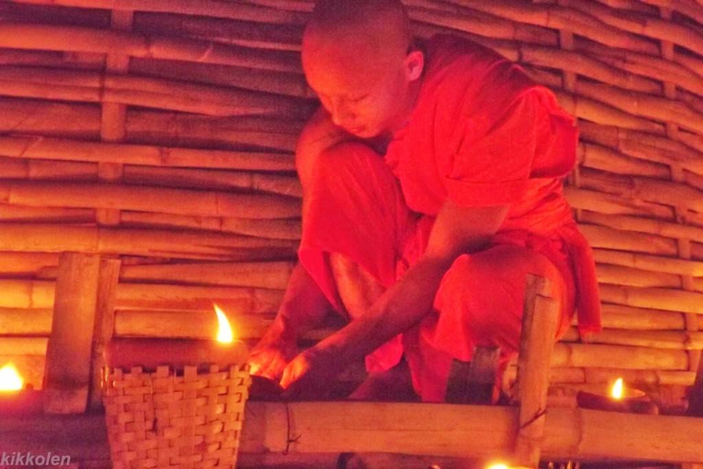 Un monaco accende le candele attorno a un chedi per la festa di Makha Bucha.